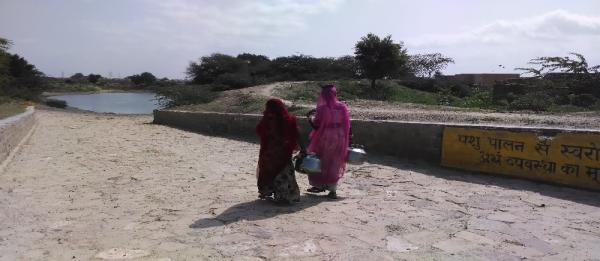 Two women walking down to the rain water reservoir